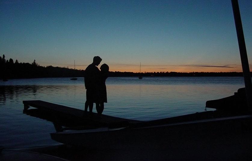 pariskunta lähekkäin veden äärellä auringonlaskussa.