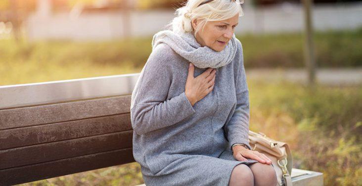 nainen istuu puistonpenkillä rintaansa pidellen.