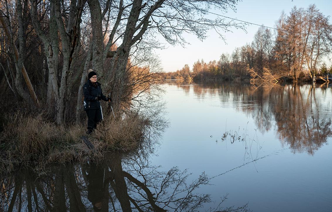 Pia Kohijoki sauvakävelyllä veden äärellä.