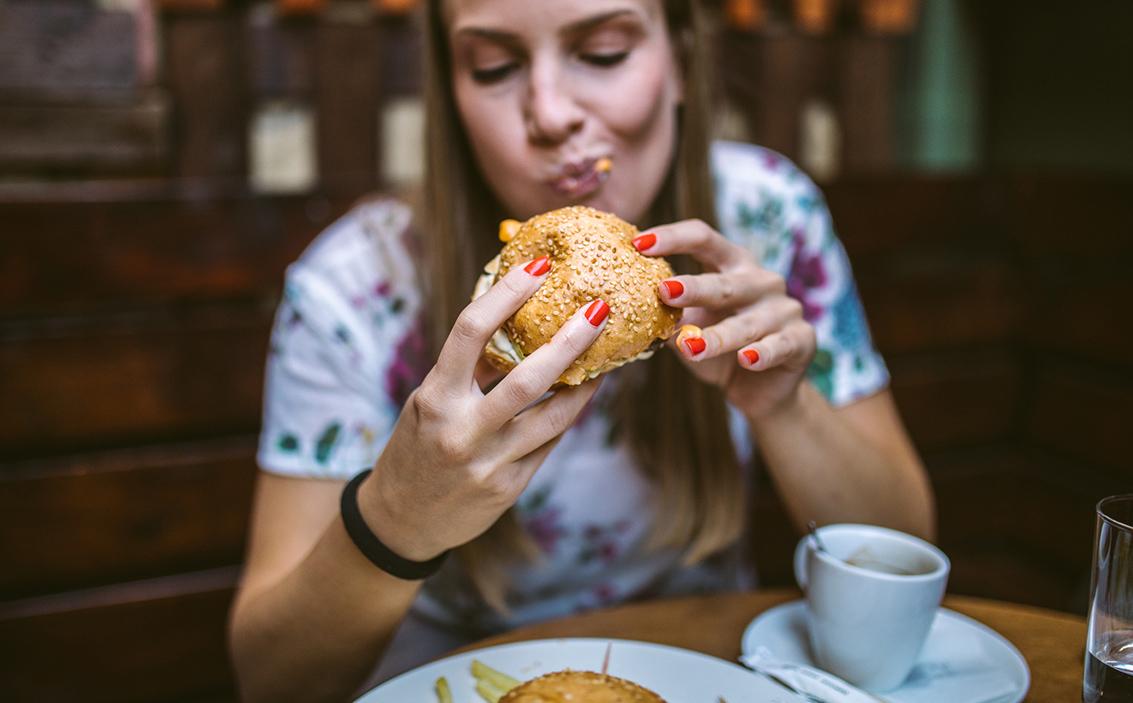 Kuvituskuva. Nainen syö hampurilaista.