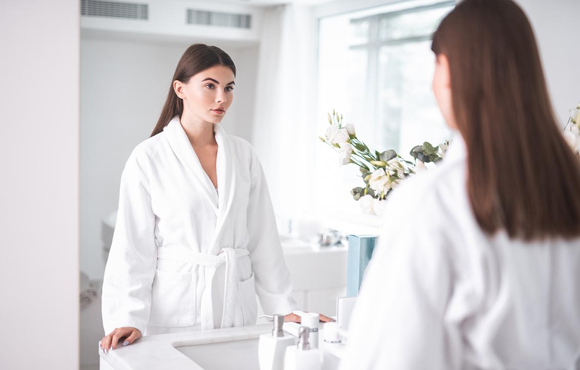 Kuvituskuva. Nainen katsoo itseään peilistä kylpytakki yllään.