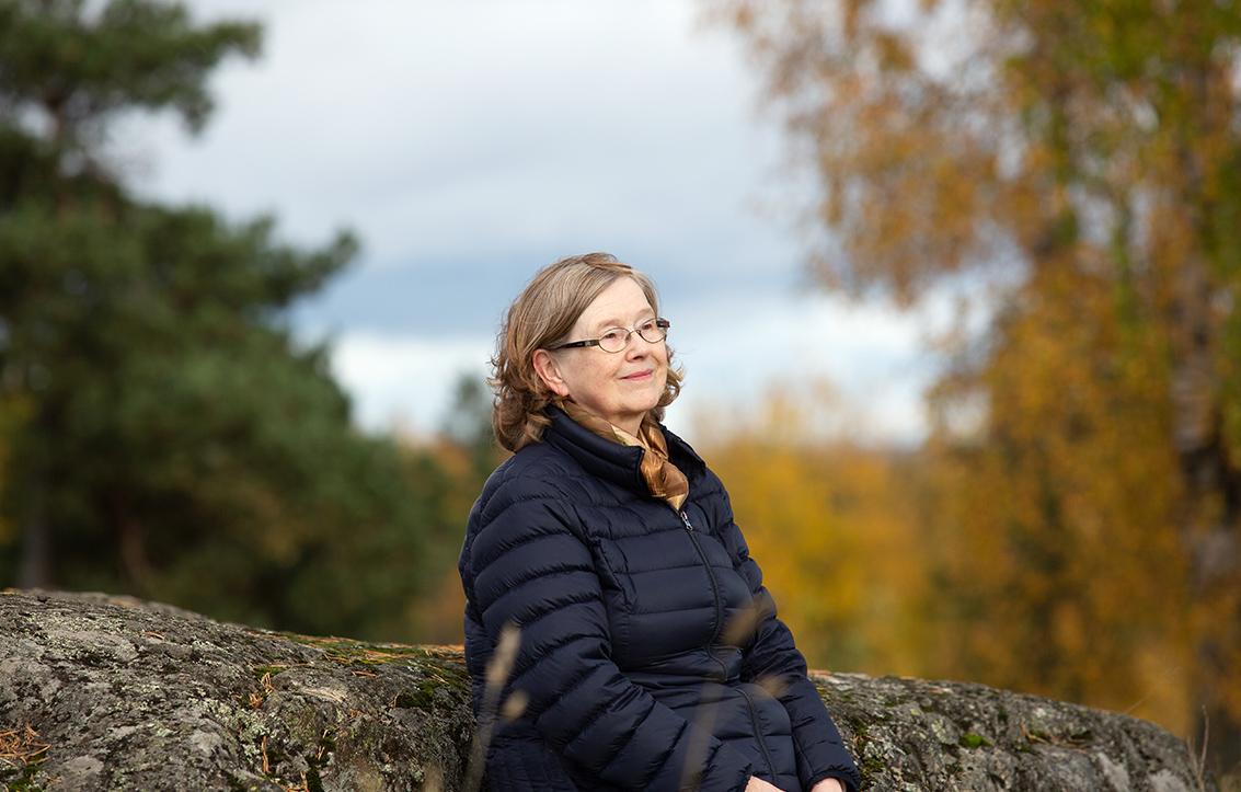 Osteoporoosia sairastava Helena Paulasto istuu kalliolla, hymyilee ja katselee kaukaisuuteen. Sää on syksyinen,