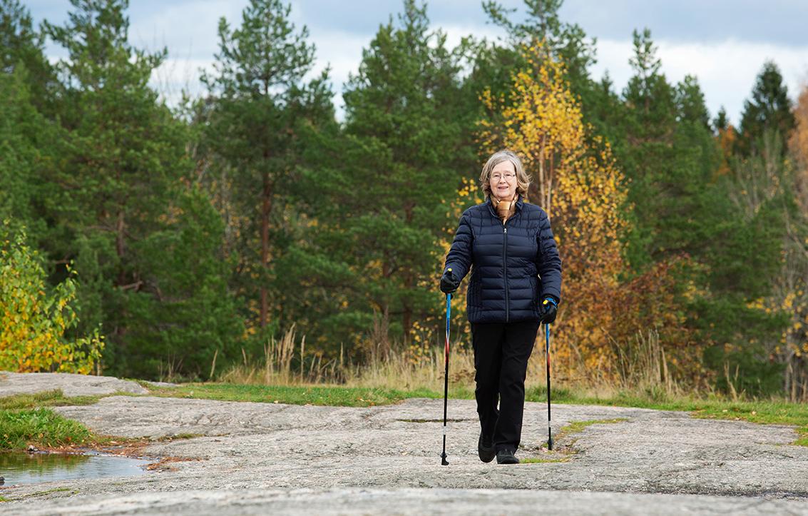 Helena Paulasto sauvakävelee syksyisessä luonnossa kalliolla. Sää on kirkas ja kuulas.