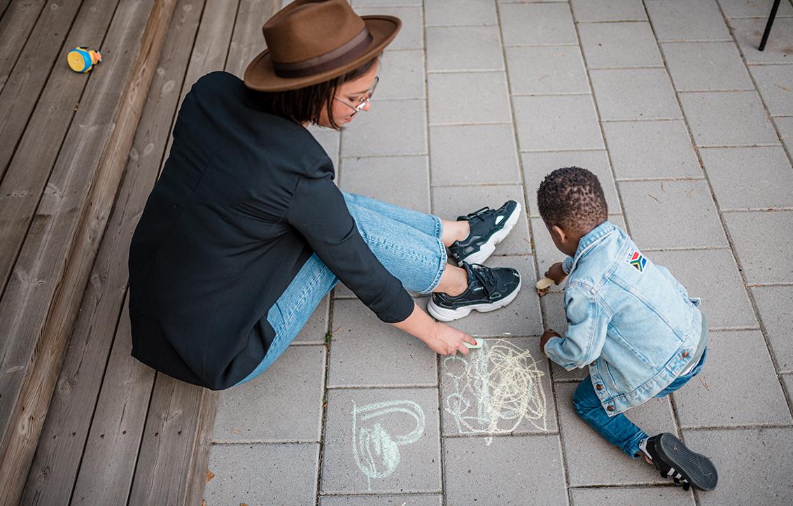 Kuvassa hattupäinen Elisa leikkii pienen pojan kanssa. Äiti istuu maasssa ja piirtää liidulla kiveykseen, poika on vierellä myös liitu kädessä.