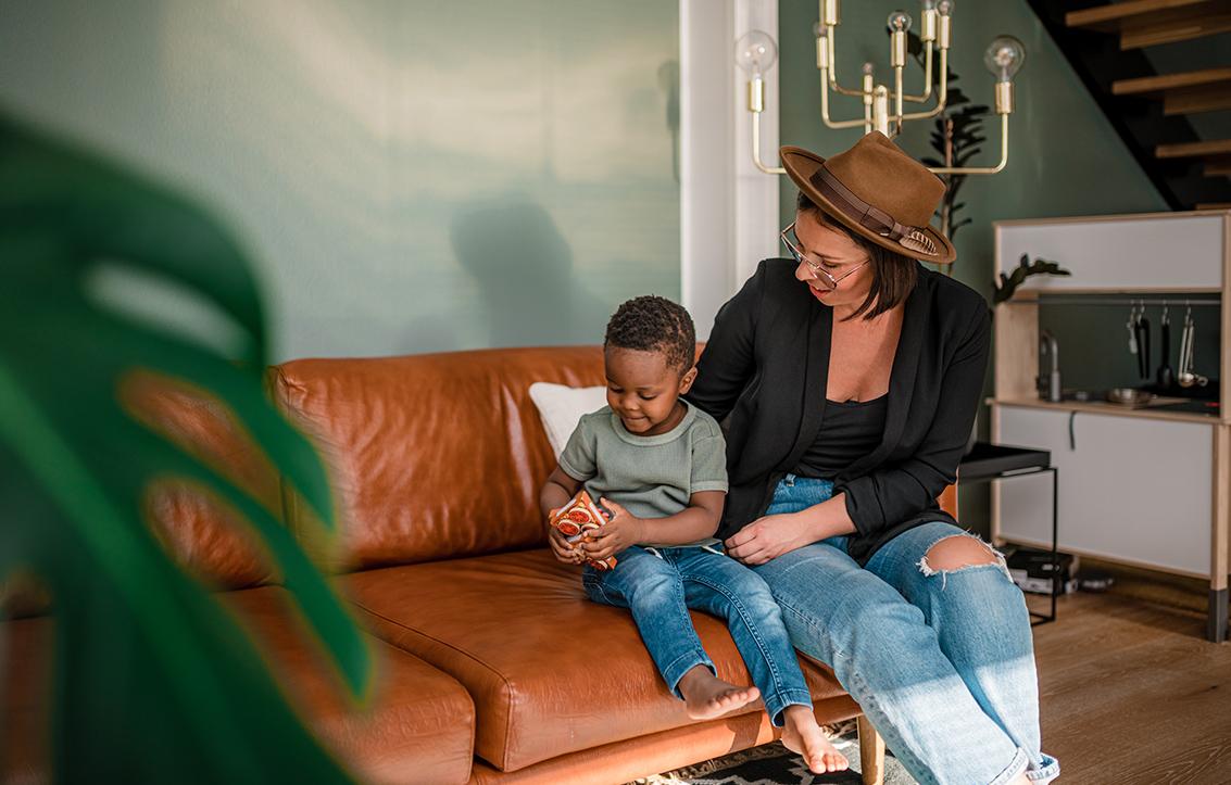 Äiti Elisa ja poika istuvat ruskealla nahkasohvalla ja katsovat pojan käsissä pitelemää esinettä.