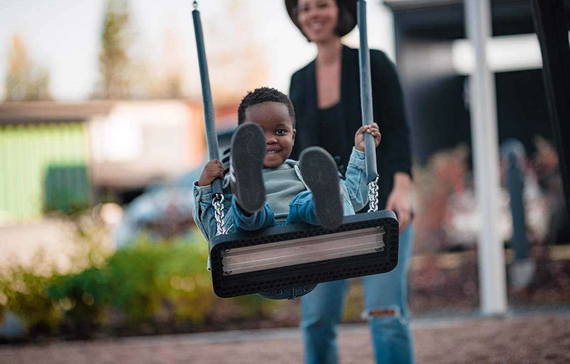 Äiti Elisa antaa vauhtia pojalle keinussa. Poika hymyilee onnellisena.