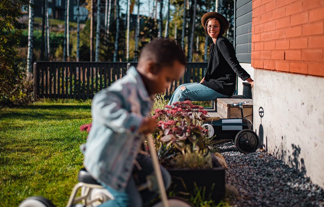 Pieni poika ajaa kolmipyörällä omakotitalon pihassa. Äiti Elisa istuu taustalla portailla, hymyilee ja katsoo poikaansa.
